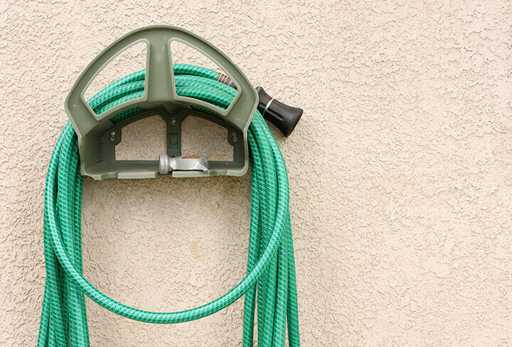 A garden hose and nozzle wound around a wall-mounted reel.