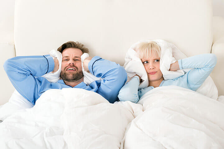 couple in bed covering their ears with pillows