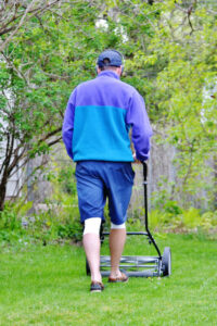 man mowing with a reel lawn mower