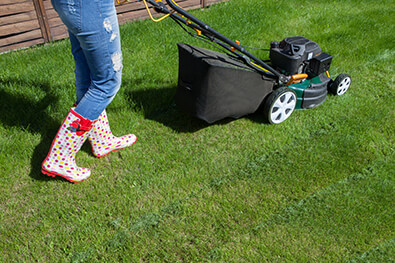 woman walking behind a lawn mower