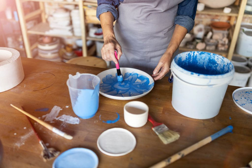 woman mixing blue paint in bowl