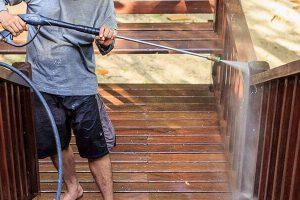 man pressure washing a deck