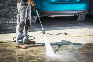 Man pressure cleaning driveway