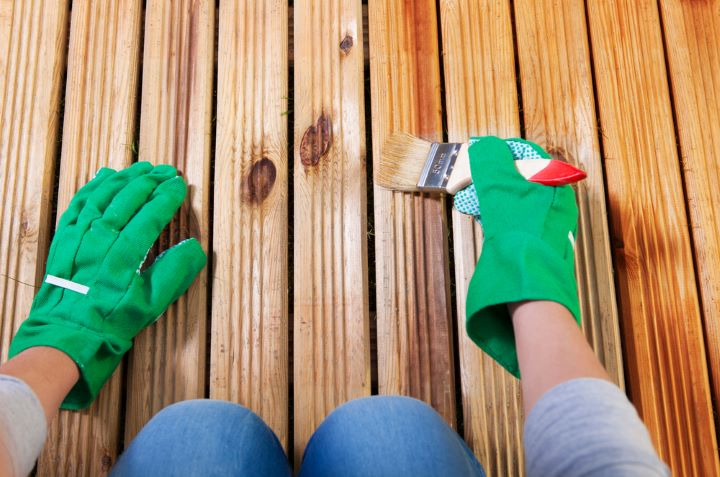Woman staining deck