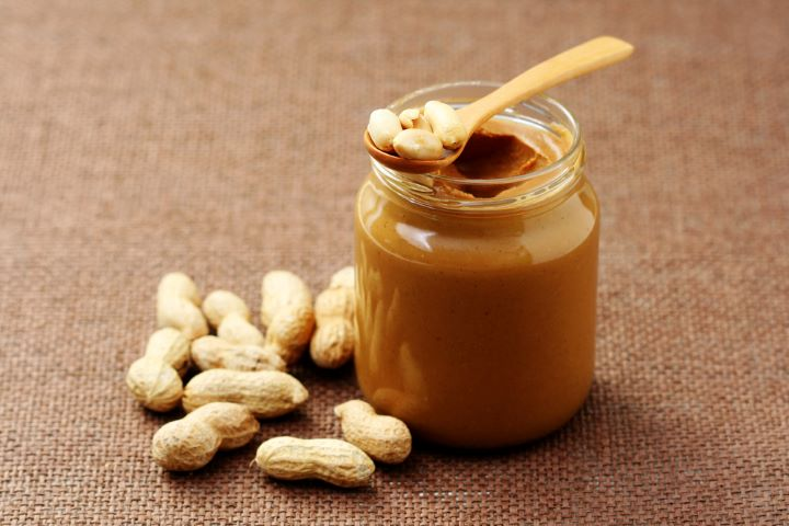 Peanuts with container of peanut butter