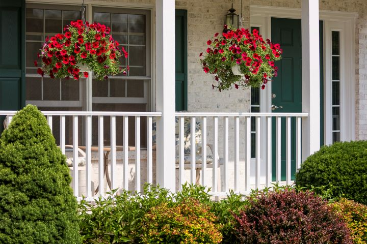 red flowers in hanging baskets on porch