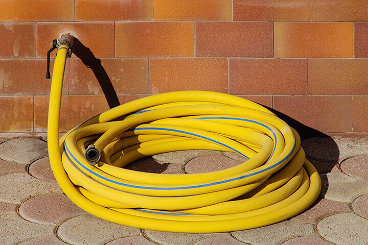 A nicely rolled up garden hose connected to an outside water facucet