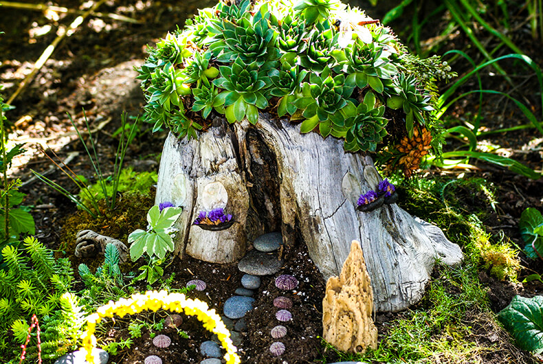 small fairy village made out of a tree stump