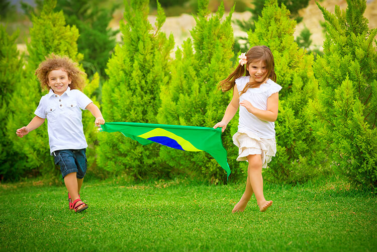 Children running outdoors with a flag