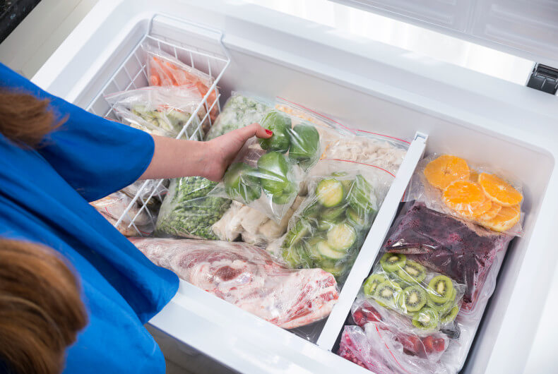 woman getting food out of a stock chest freezer