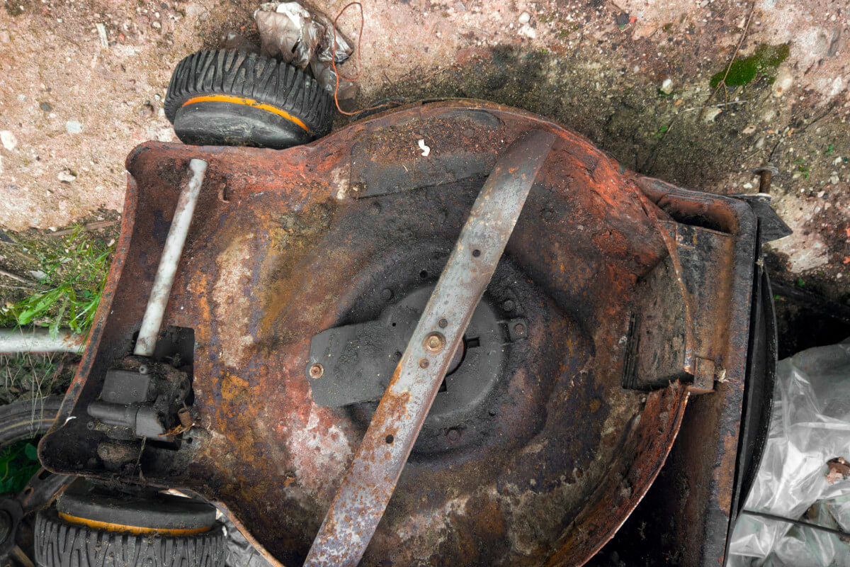 rusty undercarriage of an old lawn mower exposed to the elements