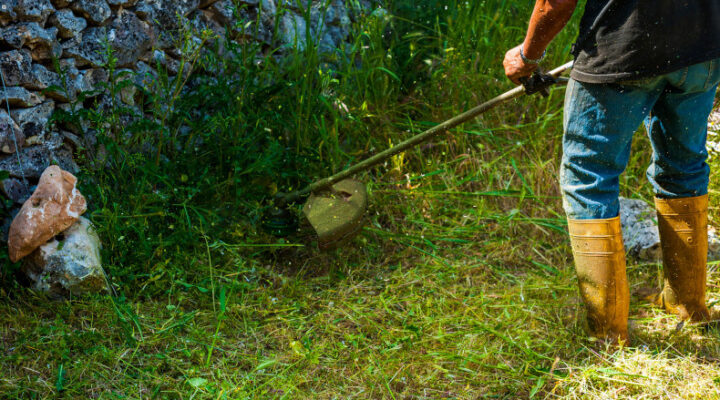 Man using a string trimmer along a stone wall