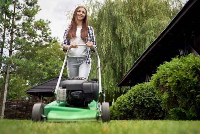 Young woman cutting grass with a lawn mower